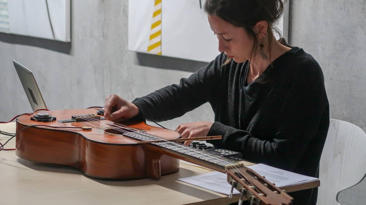 Daniela Fantechi in een performance met akoestische gitaar en piezo-elektrische microfoons